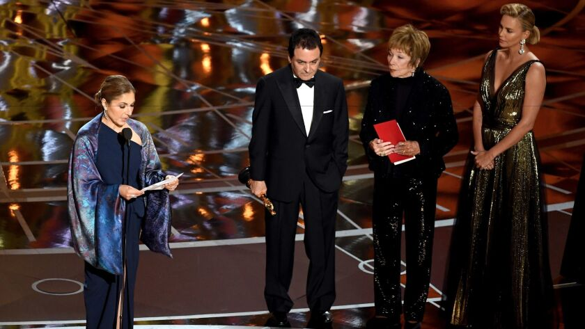 "Anousheh Ansari reads a statement on behalf of ""The Salesman"" director Asghar Farhadi, who won for foreign language film. To her right are former NASA scientist Firouz Naderi with Shirley MacLaine and Charlize Theron."