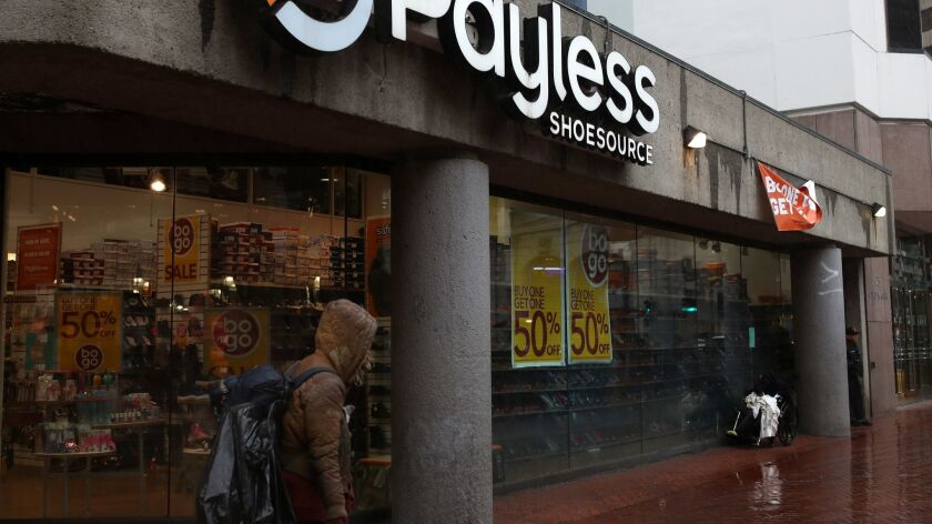 A pedestrian walks by a Payless Shoe store Feb. 8 in San Francisco. Payless is closing all of its U.S. stores.