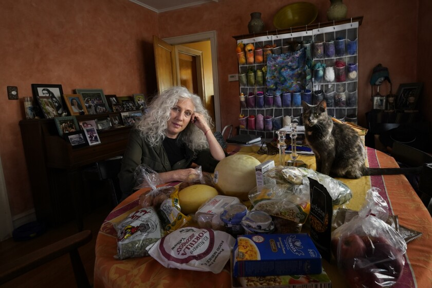 """Phyllis Marder poses with her cat, Nellie, with food she recently obtained from a local food bank in the dining room of her home in Evanston, Ill., on Thursday, Nov. 5, 2020. At first, Marder, 66, didn't tell anyone about going to food pantries. Then she had a change of heart. """"Keeping a secret makes things get worse,"""" she says '""""… and makes me feel worse about myself, and so I decided that it was more important to talk about it."""" (AP Photo/Charles Rex Arbogast)"""