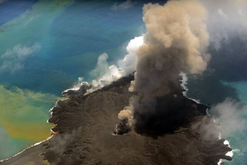This handout picture taken by Japan Coast Guard on July 23, 2014, shows the newly created islet and Nishinoshima island, which are conjoined with erupting lava at the Ogasawara island chain.