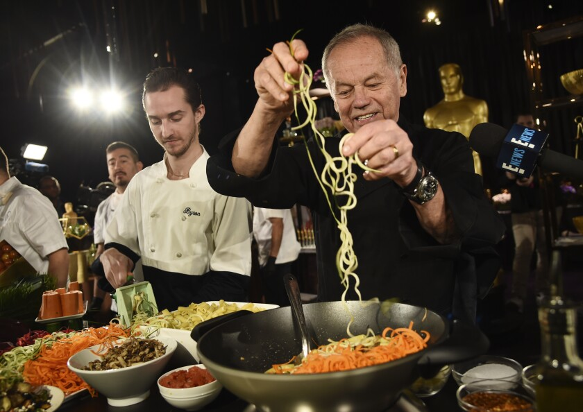 """FILE - Chef Wolfgang Puck right, and his son Byron make a pasta dish at the Governors Ball Press Preview for the 92nd Academy Awards in Los Angeles on Jan. 31, 2020. A new four-part documentary series, """"The Event,"""" shows the intense planning and details that go into high-profile catering. The series premieres on HBO Max on Jan. 14. (AP Photo/Chris Pizzello, File)"""
