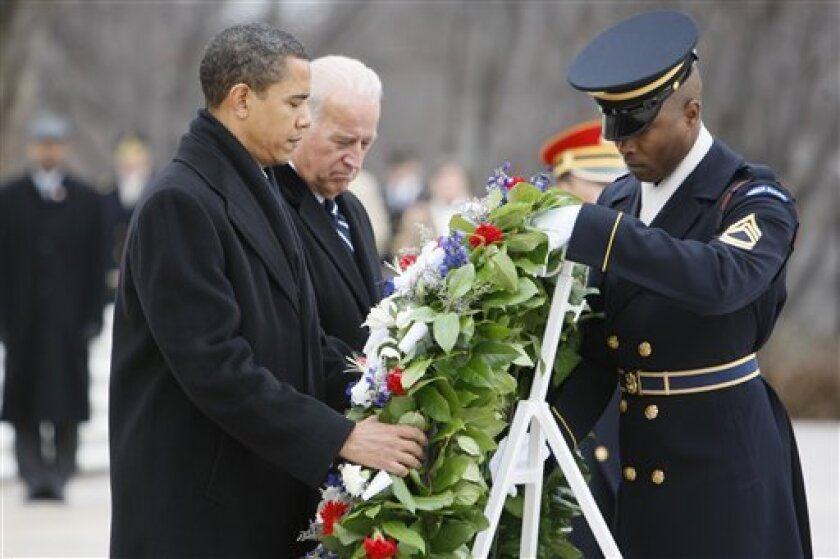 President-elect Barack Obama and Vice President-elect Joe Biden lay a wreath at the Tomb of the Unknowns at Arlington National Cemetery in Arlington, Va., Sunday, Jan. 18, 2009. (AP Photo/Charles Dharapak)