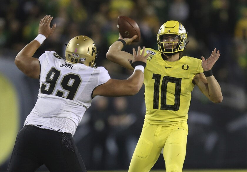 Colorado's Jalen Sami, left, rushes Oregon's Justin Herbert during the first quarter on Friday in Eugene, Ore.