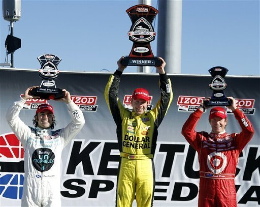 From left, Dario Franchitti, of Scotland; Ed Carpenter; and Scott Dixon, of New Zealand, stand on podium after the Kentucky 300 IndyCar Series auto race Sunday, Oct. 2, 2011, in Sparta, Ky. Carpenter won, Franchitti finished in second, and Dixon in third. (AP Photo/James Crisp)