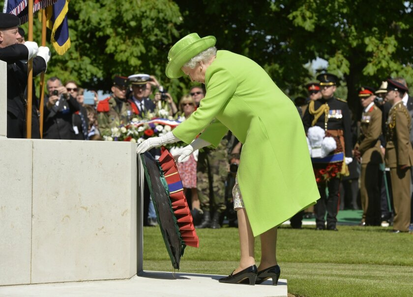 Britain's Queen Elizabeth lays a wreath during the French-British ceremony at the British War cemetery in Bayeux, Normandy, France, Friday, June 6, 2014. World leaders and veterans gathered by the beaches of Normandy on Friday to mark the 70th anniversary of World War Two's D-Day landings. (AP Photo/Thomas Bregardis, pool)