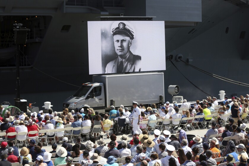 An image of Gerald R. Ford as a naval officer is shown on a video screen during the commissioning ce