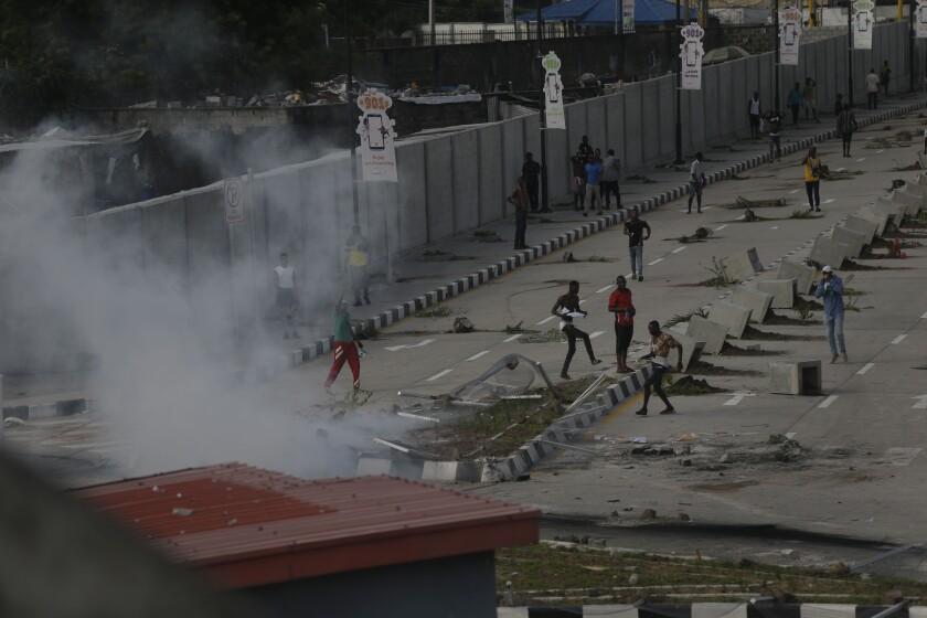 Manifestantes escapan mientras agentes de la policía emplean gases lacrimógenos