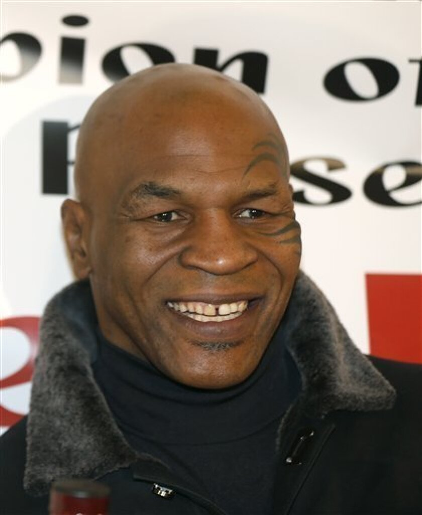 Former heavyweight champion Mike Tyson smiles during a promotional event for former five-time champion Evander Holyfield's Real Deal barbecue sauce at a Chicago grocery store Saturday, Feb. 16, 2013. (AP Photo/Charlie Arbogast)