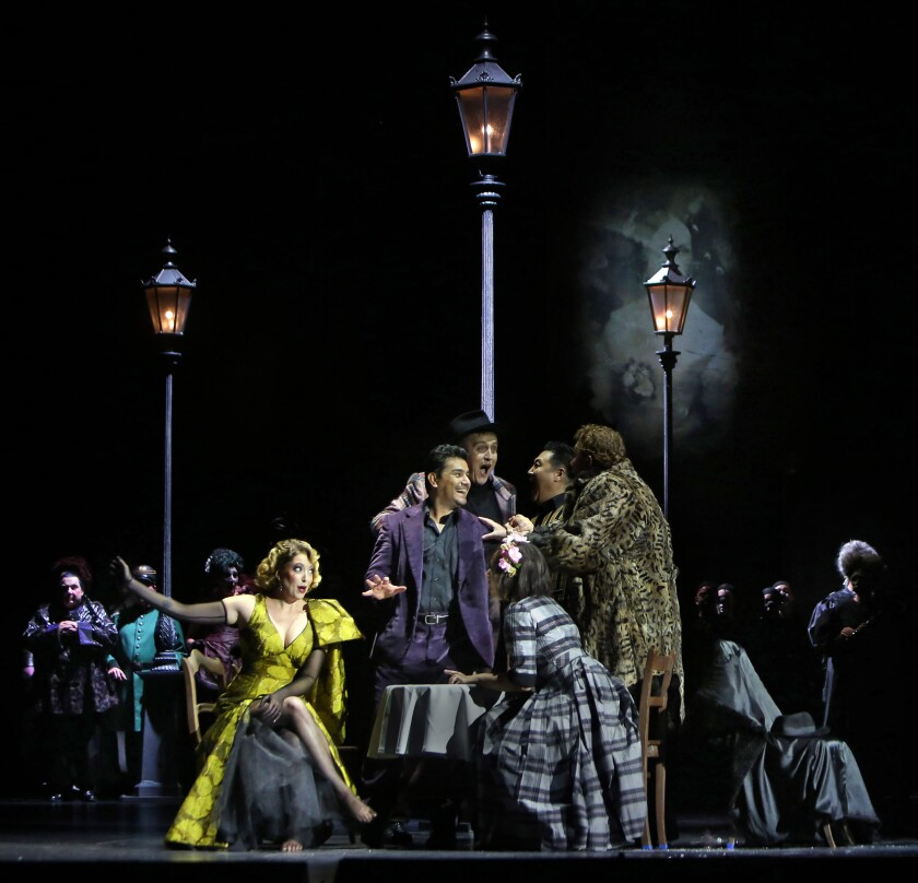 """Erica Petrocelli is Musetta (seated left), Saimir Pirgu is Rodolfo (standing center with hand out) and Marina Costa-Jackson is Mimi (seated in plaid dress) in L.A. Opera's """"La Bohéme"""" at the Dorothy Chandler Pavilion."""
