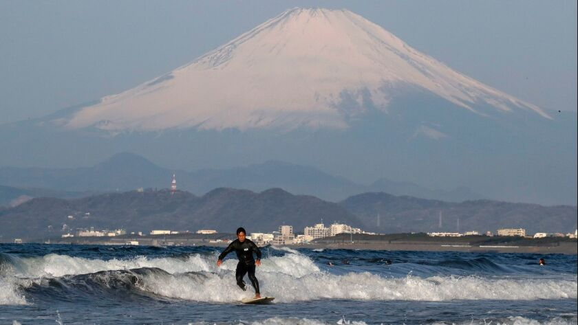A man surfs in front of Japan's Mt. Fuji on April 5. Surfing will be among the events featured in the 2020 Tokyo Olympic Games.