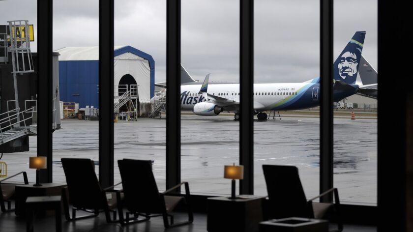 An Alaska Airlines plane undergoing maintenance is seen through a window of the new passenger termin