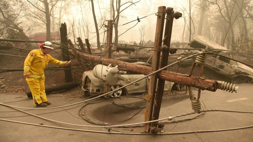 Scott Wit with the California Department of Forestry and Fire Protection surveys burned-out vehicles near a fallen power line after 2018's Camp fire, the deadliest in the state's history.