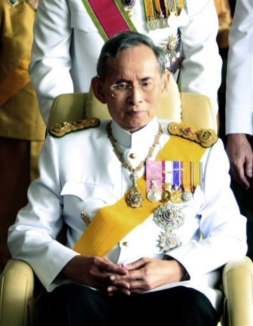 FILE - In this Dec. 5, 2010 file photo, Thailand's King Bhumibol Adulyadej is assisted while leaving Siriraj Hospital as he makes his way to the Grand Palace to attend a ceremony celebrating his 83rd birthday in Bangkok. Thai authorities said Friday, May 27, 2011, they arrested an American citizen
