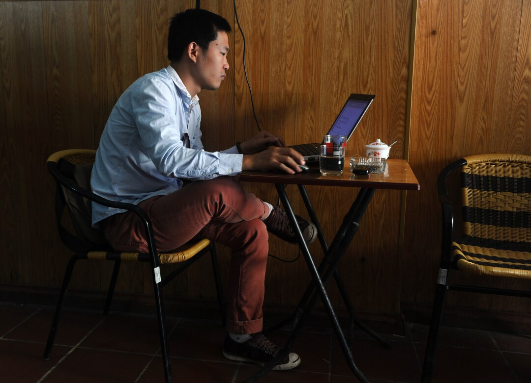 A man uses a laptop at a coffee shop in downtown Hanoi.