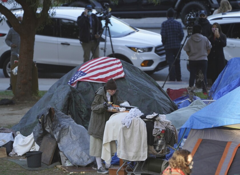 A woman eats at her tent at a homeless encampment in Los Angeles.