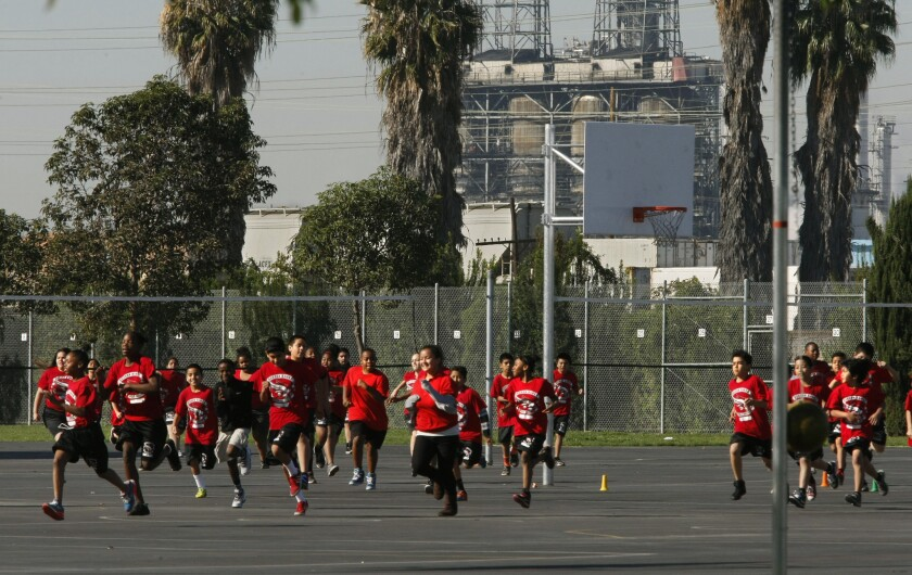 Students jog on the playground at Elizabeth Hudson K-8 Elementary School in Long Beach. The school sits near the Tesoro oil refinery, the Terminal Island Freeway, a railroad line and the Port of Long Beach. (Don Bartletti / Los Angeles Times)