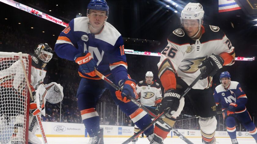 New York Islanders' Anthony Beauvillier and Ducks' Brandon Montour battle for the puck during the third period on Sunday.