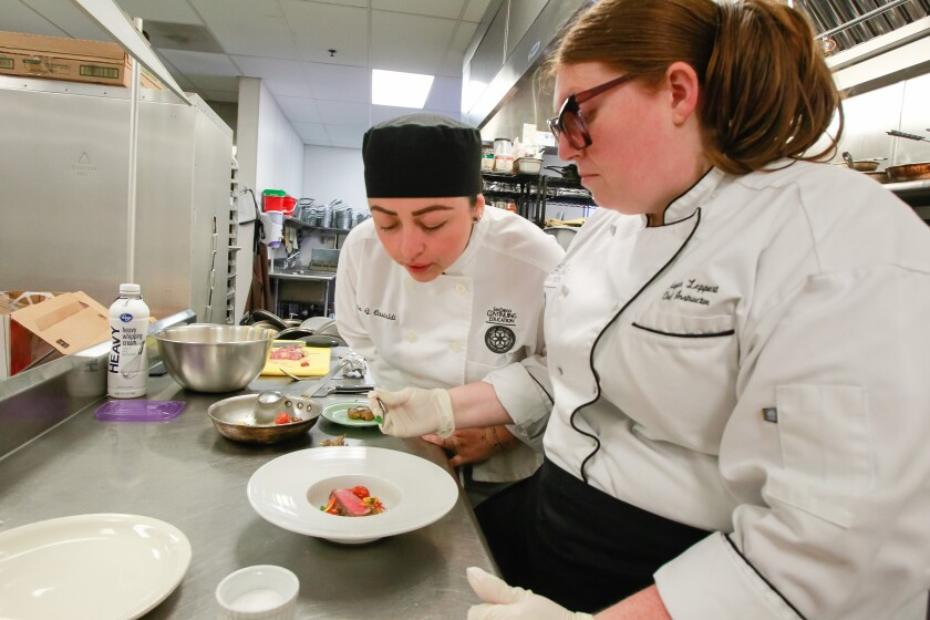 Chef instructor Megan Leppert (right) works with Nidia Castaldi in the Continuing Education culinary arts program.