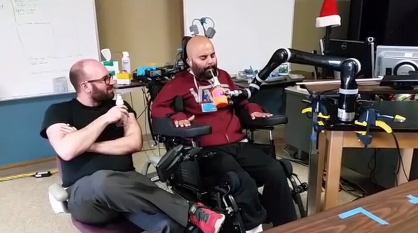 Erik Sorto enjoys a beer that he picked up himself with the help of a robotic arm he controls with his brain.
