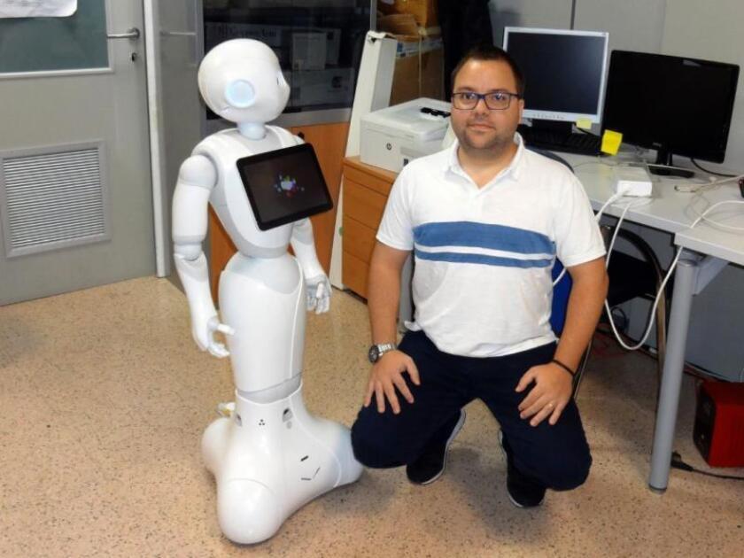 Un grupo de investigadores de Portugal y España ha creado un robot, al que han bautizado con el nombre de Pharos, con el objetivo de facilitar un envejecimiento activo y combatir la soledad en las personas mayores. En la imagen, facilitada por la Universidad Minho, Ângelo Costa, uno de los investigadores lusos, junto al robot. EFE
