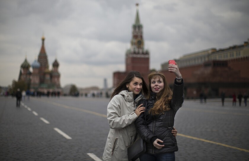 """Dos jóvenes se toman una foto en la Plaza Roja, en Moscú, el 6 de octubre de 2014. Alarmada por el número de rusos que han muerto mientras se tomaban selfies con sus teléfonos, la policía rusa ha iniciado una nueva campaña llamada """"Selfies Seguras"""", se informó el 7 de julio de 2015. (Foto AP/Alexander Zemlianichenko, Archivo)"""