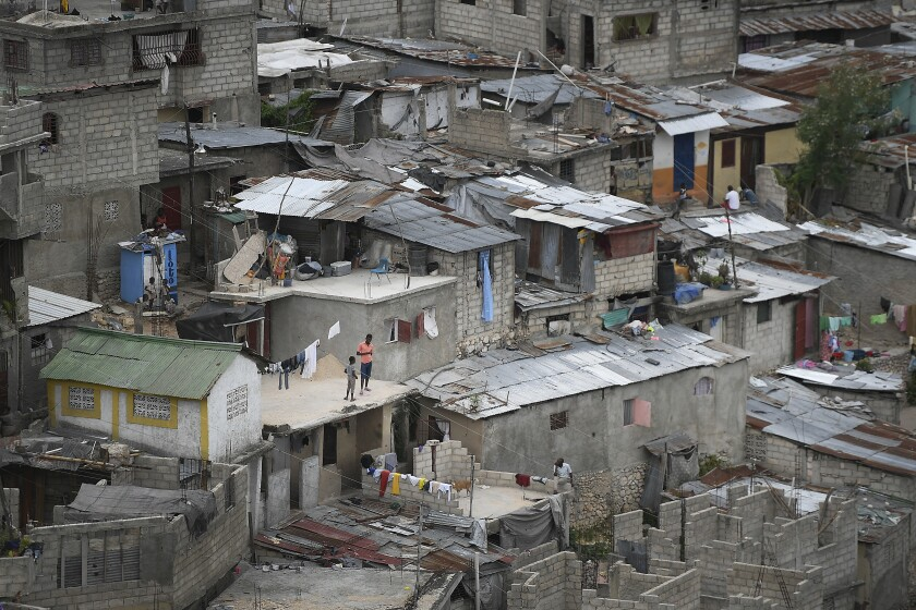 People stand on a rooftop in a crowded residential area