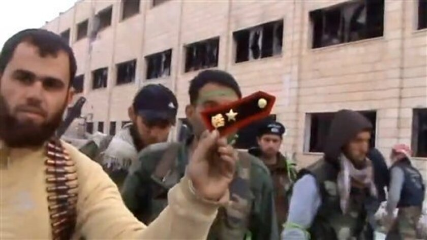 In this Sunday March 3, 2013 image taken from video obtained from the Shaam News Network, which has been authenticated based on its contents and other AP reporting, a Syrian rebel fighters displays an epaulette from a government soldier during a tour of the police academy complex in Khan al-Asal, in the province of Aleppo, Syria. The Britain-based Syrian Observatory for Human Rights said the rebels seized the police academy in Khan al-Asal after entering the sprawling government complex with cap