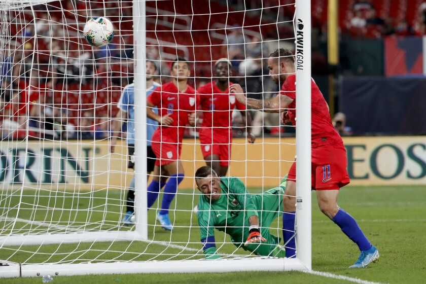 United States' Jordan Morris (11) scores past Uruguay goalkeeper Fernando Muslera during the second half of a friendly match on Tuesday in St. Louis. The game ended in a 1-1 tie.