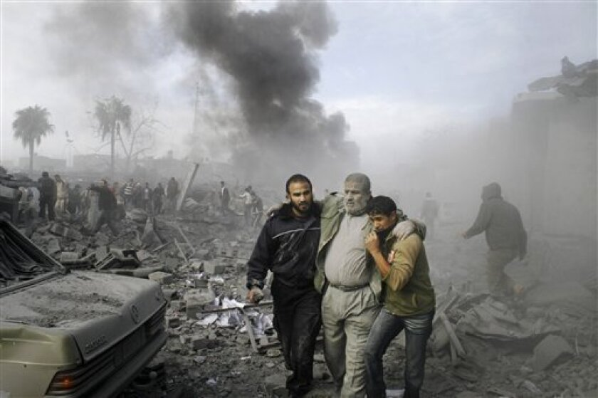 FILE - In this Dec. 27, 2008, file photo, an injured Palestinian is helped from the rubble following an Israeli missile strike in Rafah, southern Gaza Strip. Israel has failed to show it will conduct an impartial investigation of allegations that it committed war crimes during its Gaza offensive last winter, an international human rights group said Sunday, Feb. 7, 2010. (AP Photo/Hatem Omar, File)