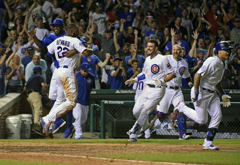 Chicago Cubs Jason Heyward celebrates with teammates after he scored on a sacrifice bunt hit by Jon Lester (34) in the twelfth inning of a baseball game against the Seattle Mariners on Sunday, July 31, 2016, in Chicago. The Chicago Cubs beat the Seattle Mariners 7-6. (AP Photo/Matt Marton)