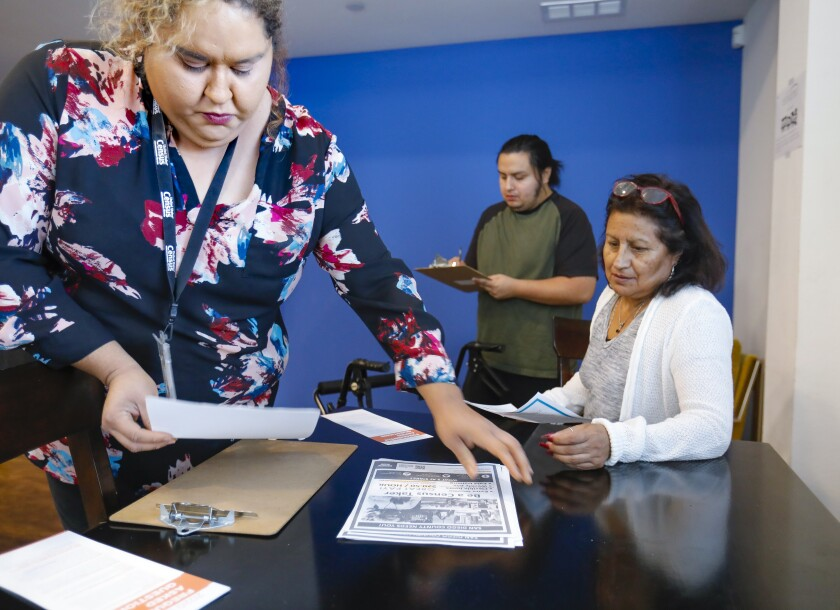 Joel Bird, center, and his mother, Patricia Bird, right, apply to become census-takers. The U.S. Census Bureau's Iriz Lomeli, right, explains the job.