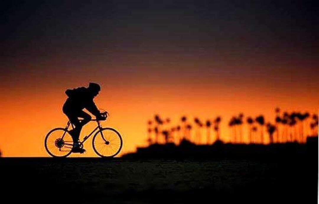 A cyclist rides along Belmont Shore, with Island Chaffee in the background.