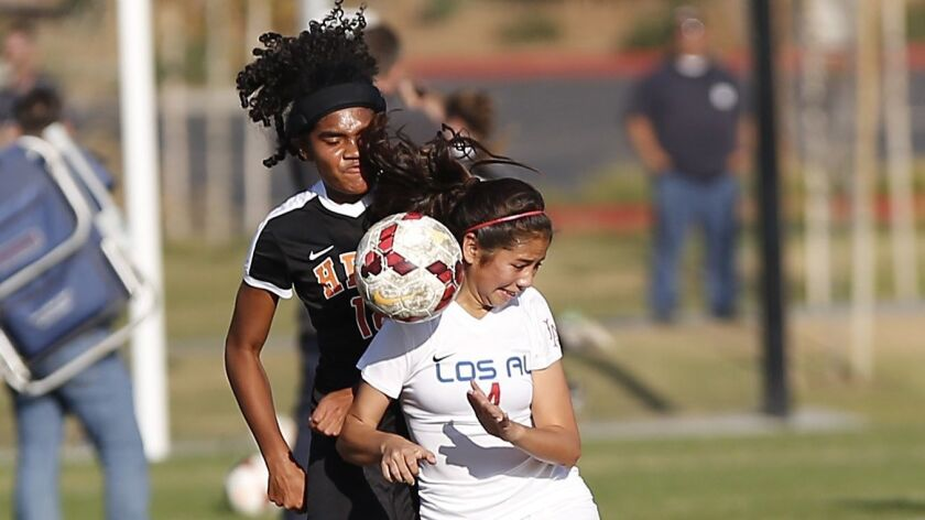 Huntington's Kekoa Nelson, left, collides with a Los Alamitos defender as they go for ball control d