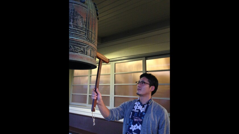 The Rev. Takafumi Bansaka strikes a bell outside the Higashi Hongwanji Mission in Honolulu. Each year Buddhists ring in the new year by acknowledging mankind's 108 evil passions.