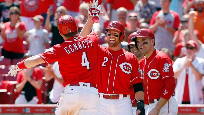 Cincinnati Reds second baseman Scooter Gennett (4) is congratulated by shortstop Zack Cozart (2), first baseman Joey Votto (19) and right fielder Jesse Winker (33) after Gennett hit a grand slam against the San Diego Padres during the seventh inning at Great American Ball Park.