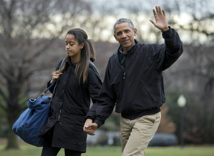 FILE - In this Jan. 4, 2015 file photo, President Barack Obama, with his daughter Malia Obama, waves as they arrive at the White House in Washington. President Barack Obama is missing out on a big part of his daughter's life: joining her college campus tours as she tries to figure out where to stud
