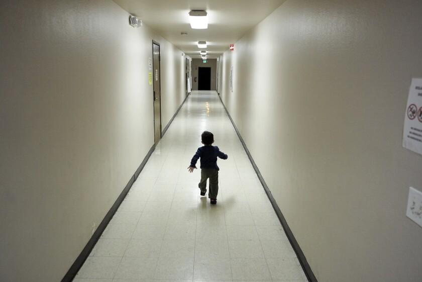 An asylum-seeking boy from Central America runs down a hallway