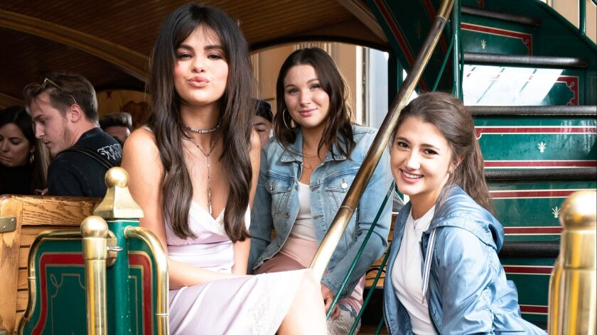 Selena Gomez, left, made a personal appearance at the Grove in Los Angeles to celebrate her new capsule collection of clothes and accessories with Coach.
