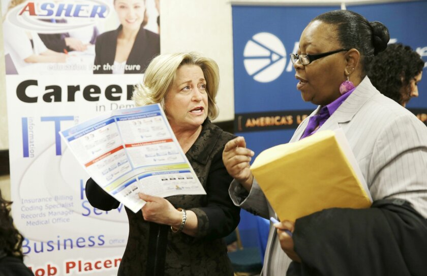 FILE - This Jan. 22, 2014, file photo, shows recruiter Valera Kulow, left, speaking with job seeker Monic Spencer during a career fair in Dallas.