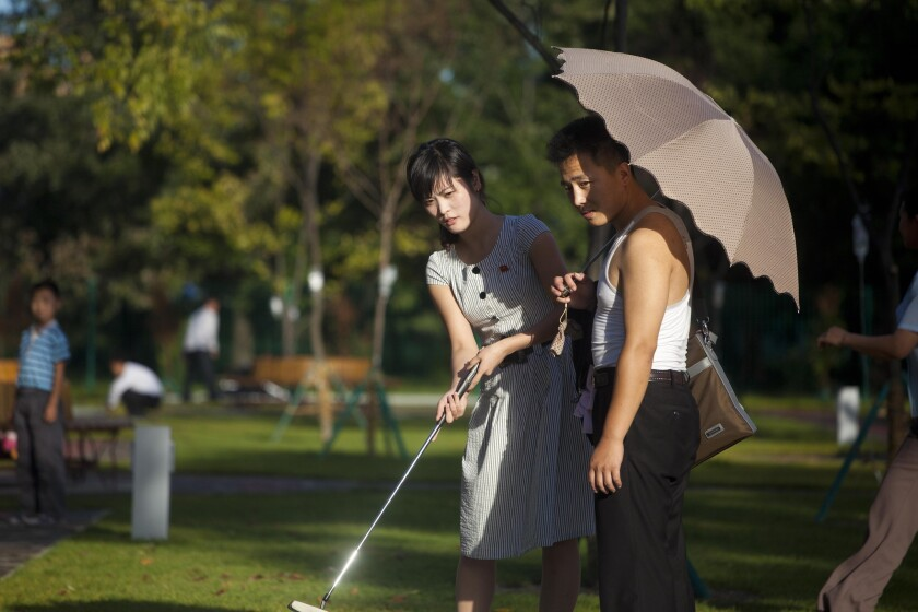 In this Sept. 8, 2012, photo, a man holds a woman's bag and parasol as they play miniature golf at a newly built amusement park in Pyongyang, North Korea.