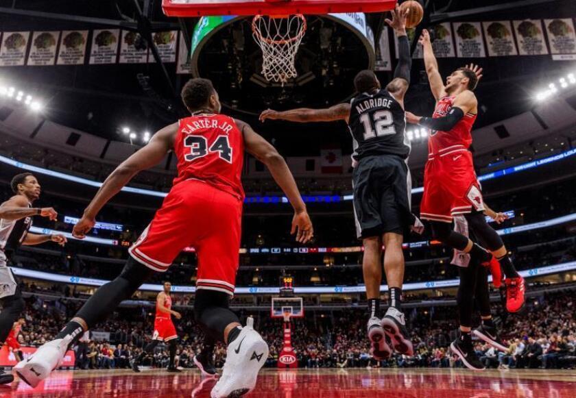 El escolta Zach LaVine (d) y el alero Wendell Carter Jr. (i) de San Antonio Spurs en acción ante el alero LaMarcus Aldridge (c) de Chicago Bulls durante un juego de la NBA entre San Antonio Spurs y Chicago Bulls, en el United Center de Chicago, Illinois (EE. UU.). EFE