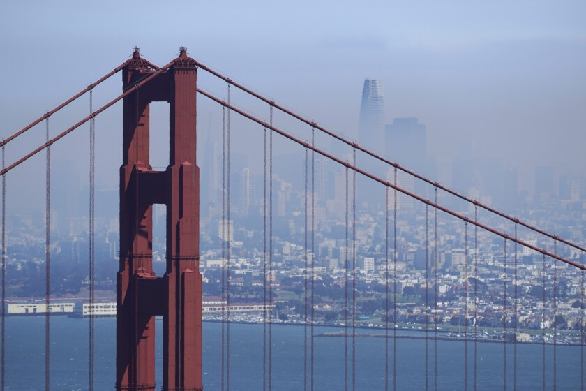 The San Francisco skyline, with the Golden Gate Bridge in the foreground, is obscured by smoke from the wildfires.