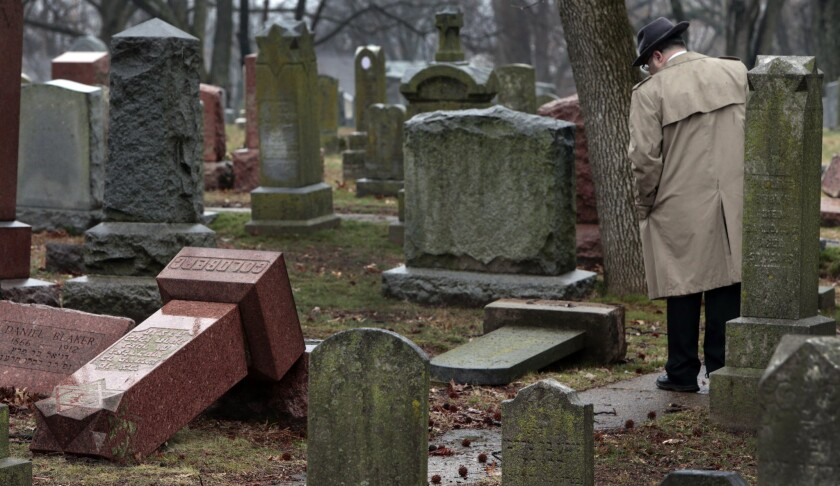 People walk through toppled graves at Chesed Shel Emeth Cemetery in University City on Tuesday, Feb. 21, 2017 where almost 200 gravestones were vandalized over the weekend.