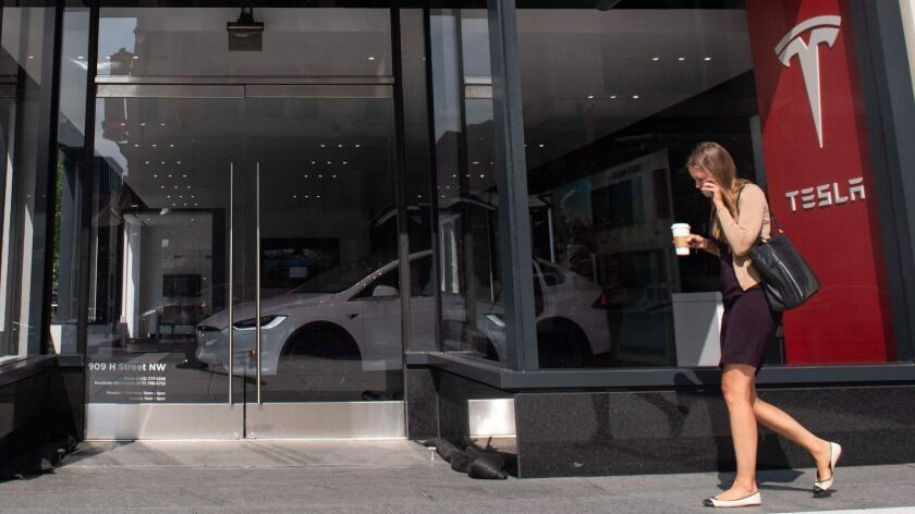 A woman walks past a Tesla showroom in Washington, D.C.