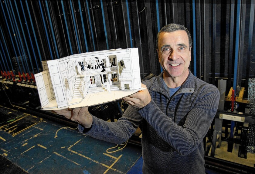 """Set designer Tom Buderwitz holds up a miniature set model to the upcoming play """"Whipping Man"""" at South Coast Repertory in Costa Mesa."""