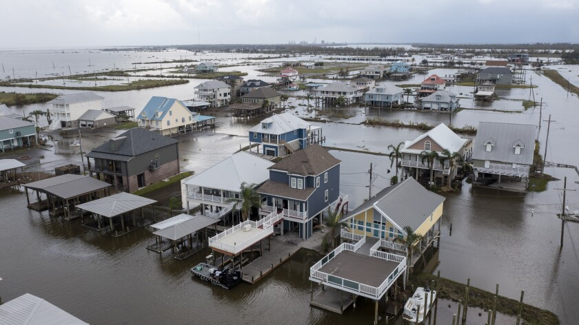 Flood waters still surround homes as residents try to recover from the effects of Hurricane Ida Wednesday, Sept. 1, 2021, in Myrtle Grove, La. (AP Photo/Steve Helber)