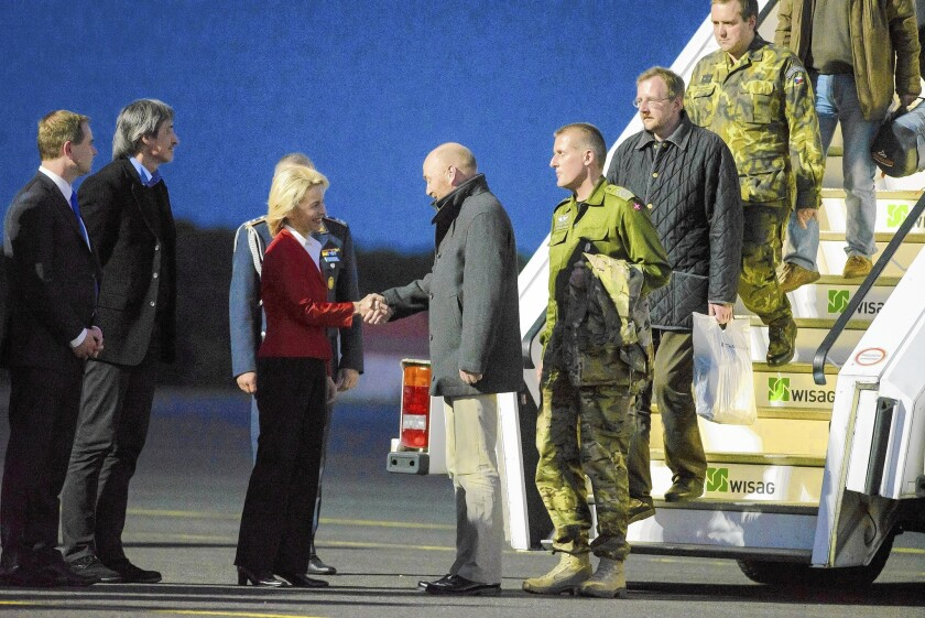 At Berlin's Tegel Airport, German Defense Minister Ursula von der Leyen greets freed observer Axel Schneider and other members of the OSCE team on May 3, 2014, after their release from captivity in eastern Ukraine.
