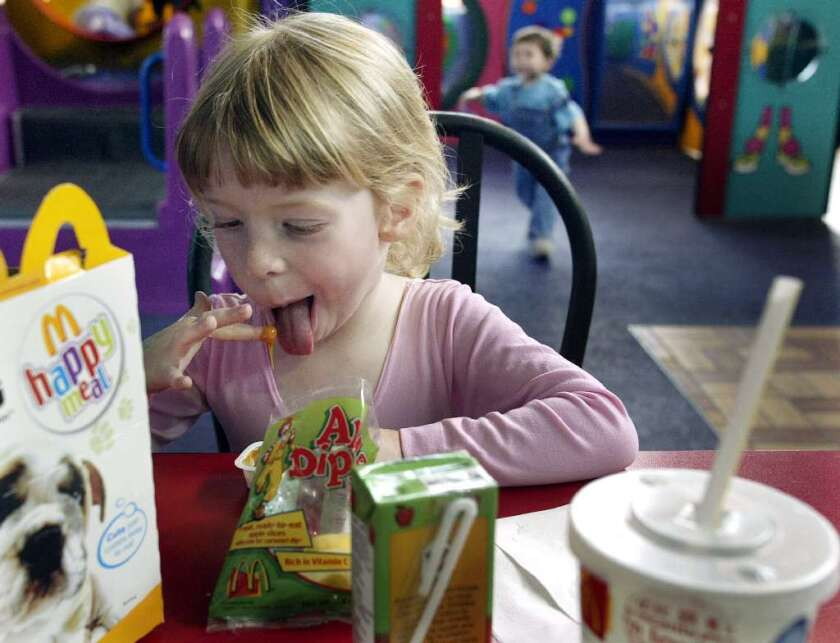 A new report on fast food for kids and teens praises McDonald's for reducing French fry portions and adding apple slices to all Happy Meals. But overall, the fast-food industry has a long way to go, researchers say.