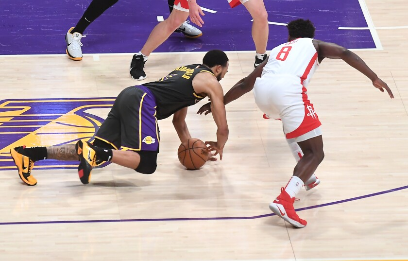Players dive for a loose basketball.