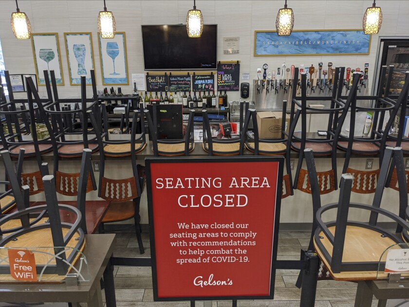 FILE - In this March 26, 2020, file photo, an indoors sitting bar is closed inside the Gelson's Market in the Los Feliz neighborhood of Los Angeles. Los Angeles County announced new coronavirus-related restrictions Sunday, Nov. 22, 2020, that will prohibit in-person dining for at least three weeks as cases rise at the start of the holiday season and officials statewide begged Californians to avoid traveling or gathering in groups for Thanksgiving. LA County's new rules take effect Wednesday at 10 p.m., restaurants, breweries, wineries and bars will only be able to offer takeout, drive-thru, and delivery services. (AP Photo/Damian Dovarganes, File)